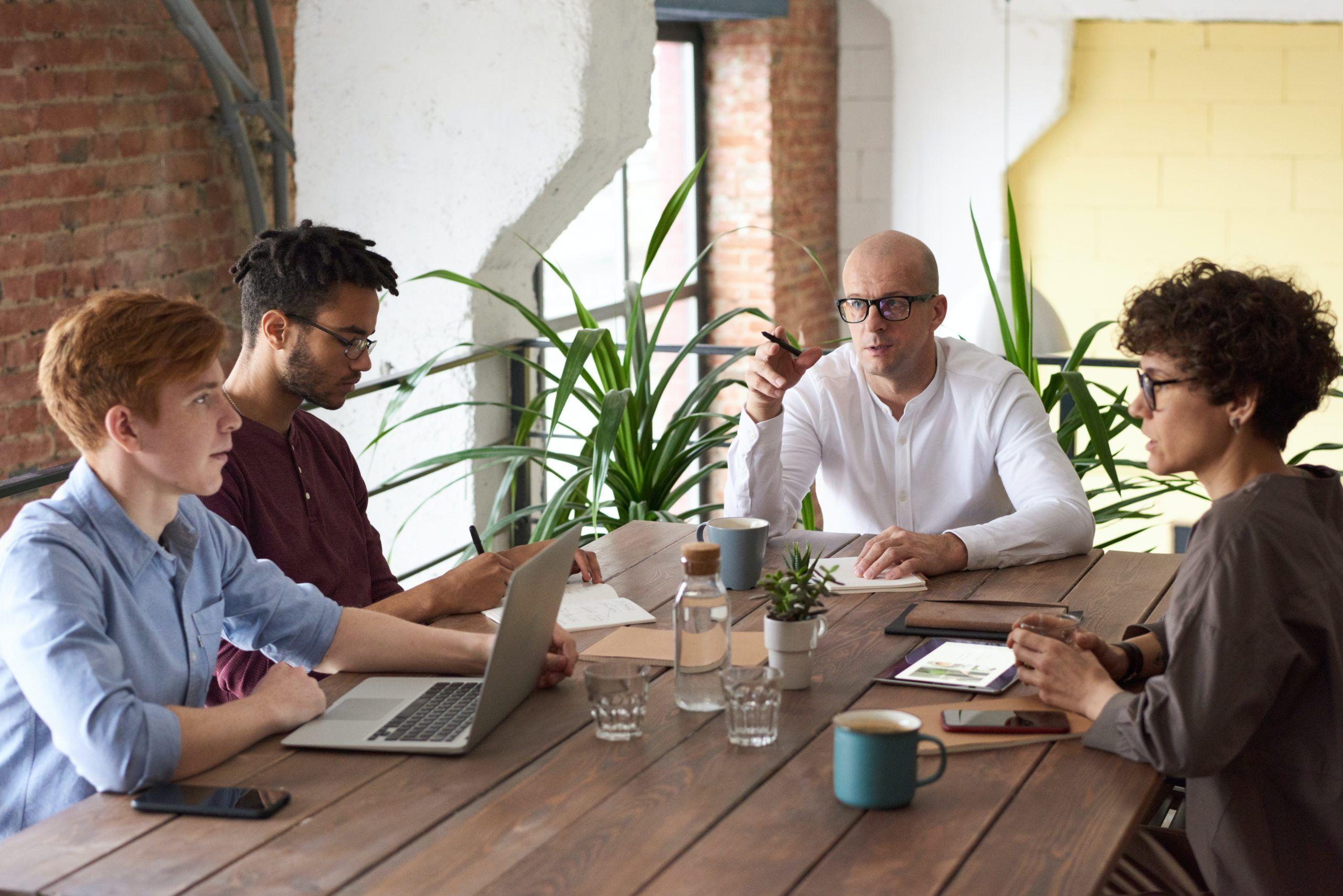 cuatro personas hablando en una oficina en un buen ambiente laboral