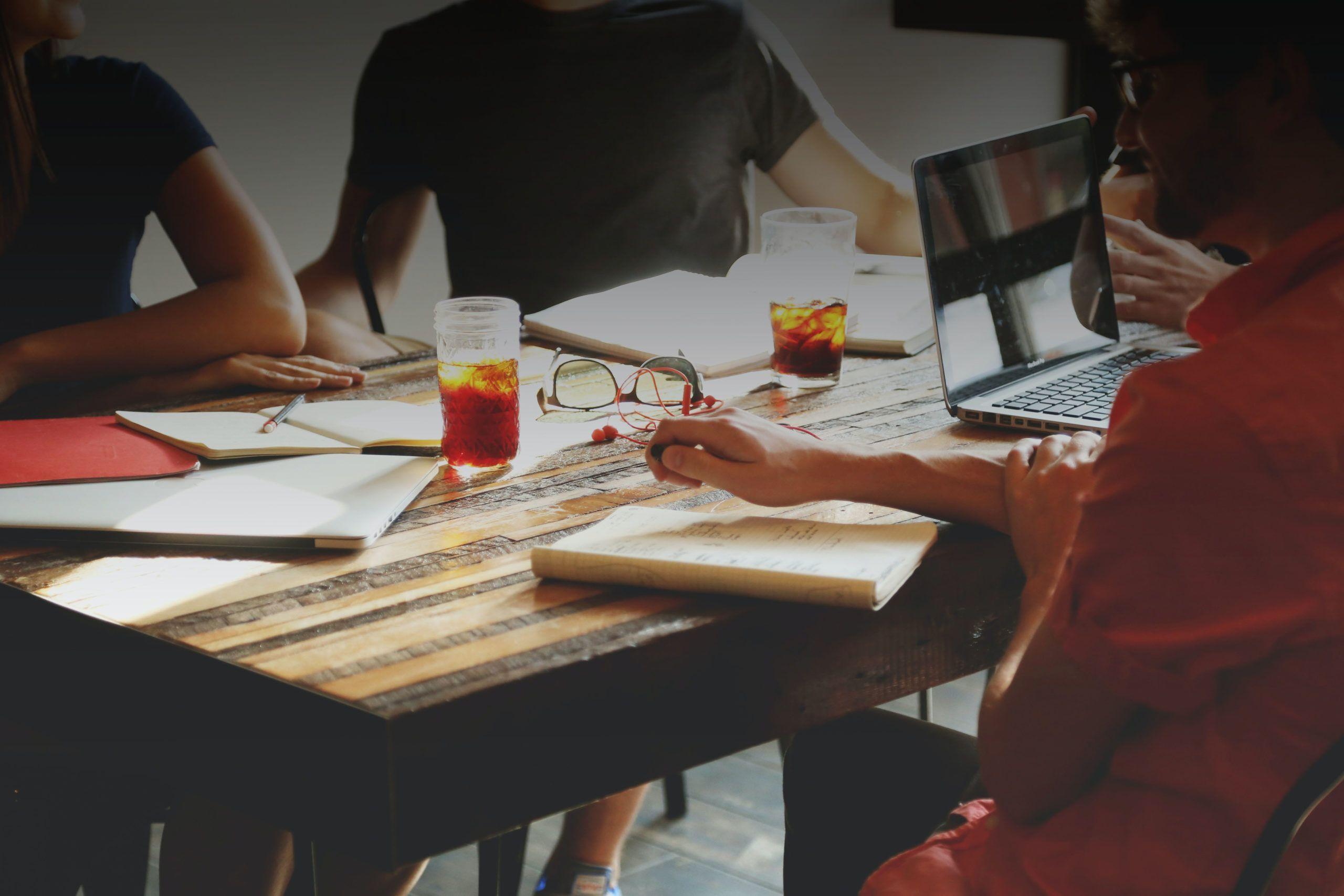 Personas trabajando juntas en una mesa de madera grande con cuadernos y bebiendo té