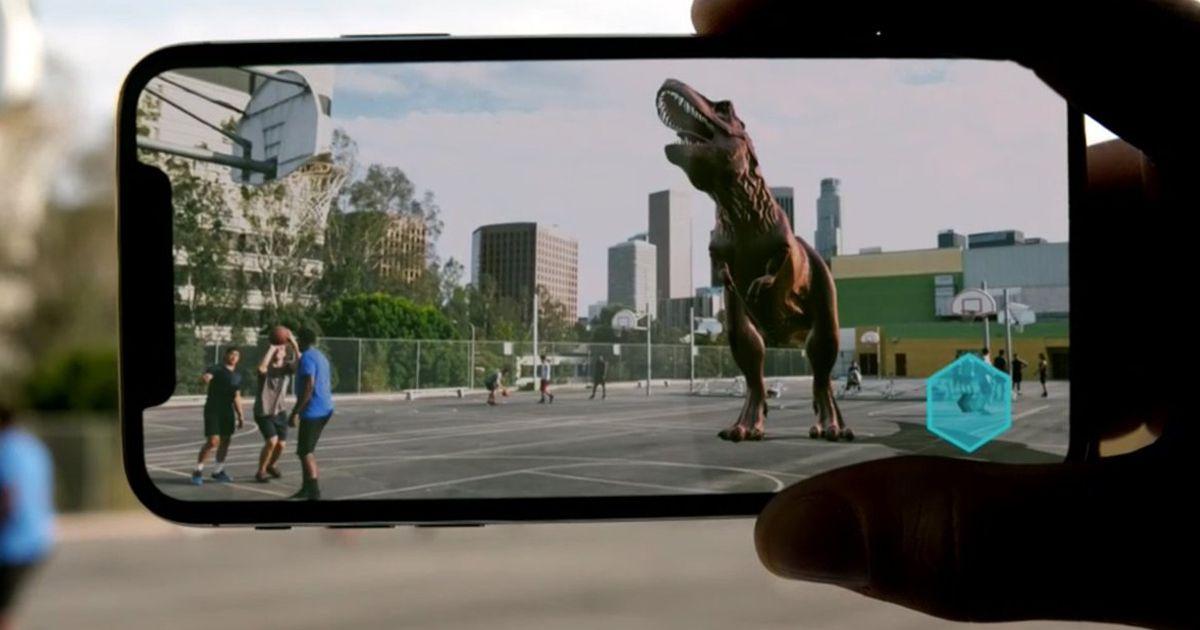 Ejemplo de realidad aumentada a través de un dispositivo celular que muestra un modelo 3D de un Tiranosaurio Rex en una cancha de futbol, casi perfectamente acoplado al entorno
