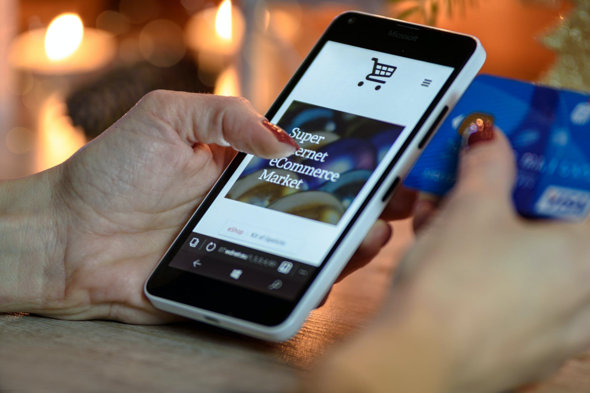 una mujer sosteniendo un celular y una tarjeta de crédito